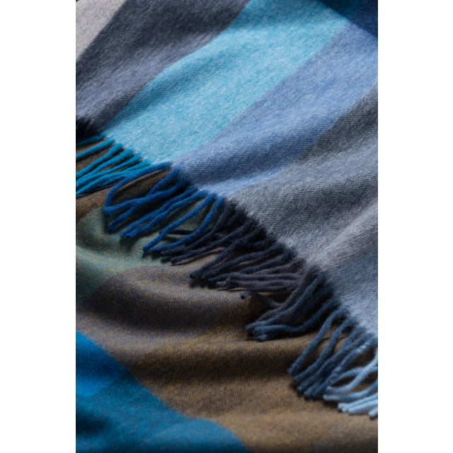 The Jura Palette blanket in Blue Multi from Begg x Co is woven from a blend of 75% superfine lambswool and 25% angora,...