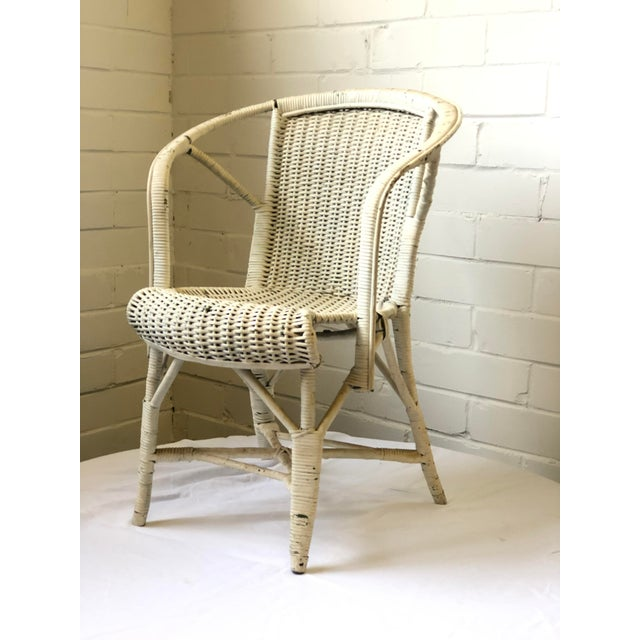 Stylish 20th Century child's bergere style chair of wicker in antique white. Original condition. Would be a great sunroom...