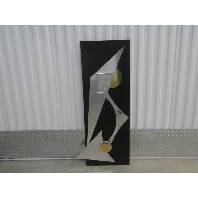 Wild chrome and brass modernist kinetic wall sculpture. The piece is signed and sold as found in vintage condition showing...