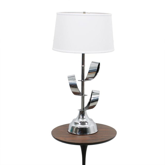 Here is a fun and cheerful chrome table lamp from the '70s. Around the central pole are three chrome ribbons or leaves,...