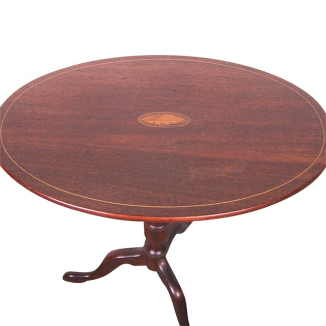 Offered is a rare early 20th Century tilt top table constructed from mahogany that features a shell inlaid marquetry on...