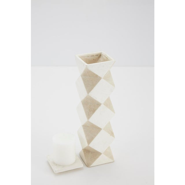 Medium-sized pillar candle holder. Body is comprised of a rectilinear cube with faceted sides, alternating white and beige...