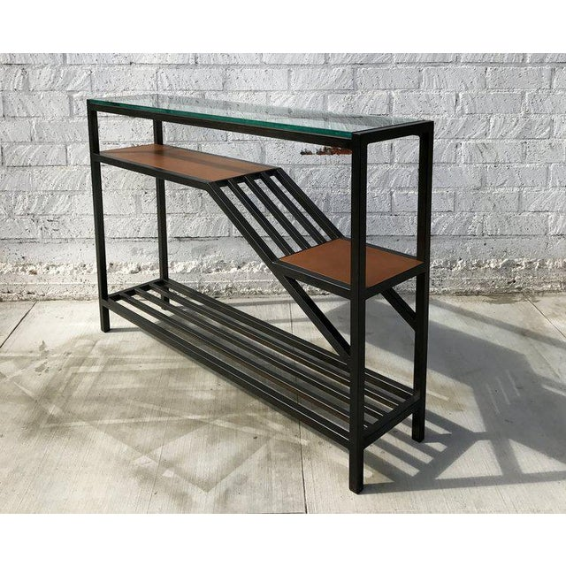 The Lloyd Entry Table is designed to convey a mixture of textures and geometric shapes with its multilevel shelving,...