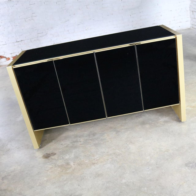Elegant small credenza or server cabinet attributed to Ello in black glass and gold anodized and brushed aluminum. It is...