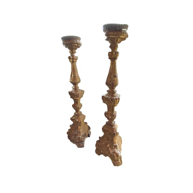 A pair of antique, circa 1880 gilt candlesticks with metal tops. Tall with triangular shape at base. Most like from a...