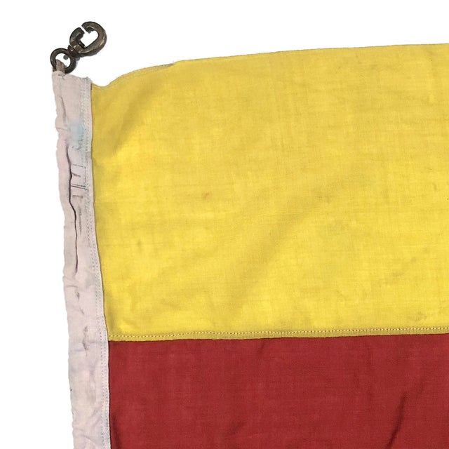 This collection of mid-century nautical flags was flown by the British Navy. Overall staining and distress reflect a...