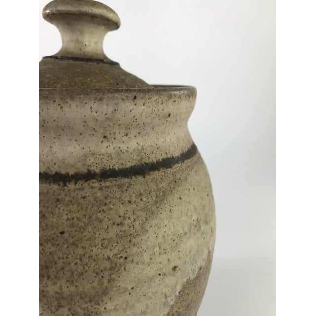 Gorgeous stoneware studio pottery canister done is a lovely tan color accented with brown stripes on the lid and neck....