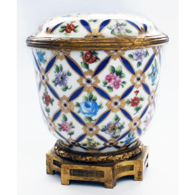 """A porcelain covered jar with overall floral enamel-like pattern and gold accents. On the lid is a portrait signed """"KA.""""..."""