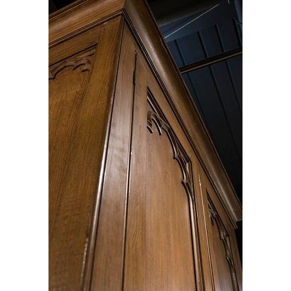 English Tall Two Door Gothic Style Armoire with Paneled Doors and Sides and Gothic Detail Openign Up to Shelving