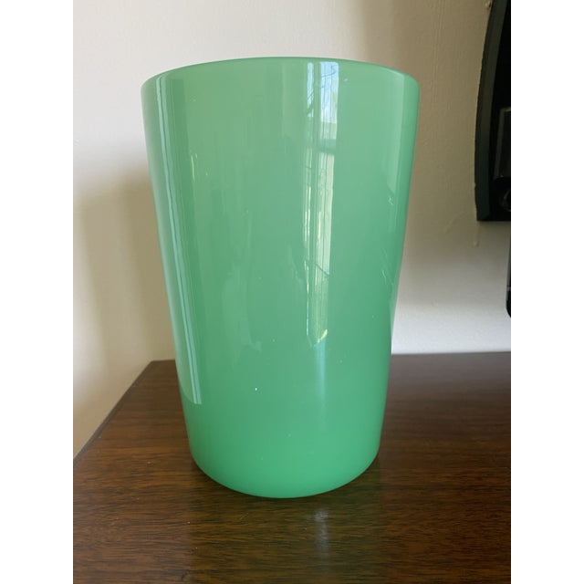 """This is a hand blown green glass cylinder vase. Dimensions are 7"""" tall and 4.75"""" diameter. Excellent condition. No marks."""
