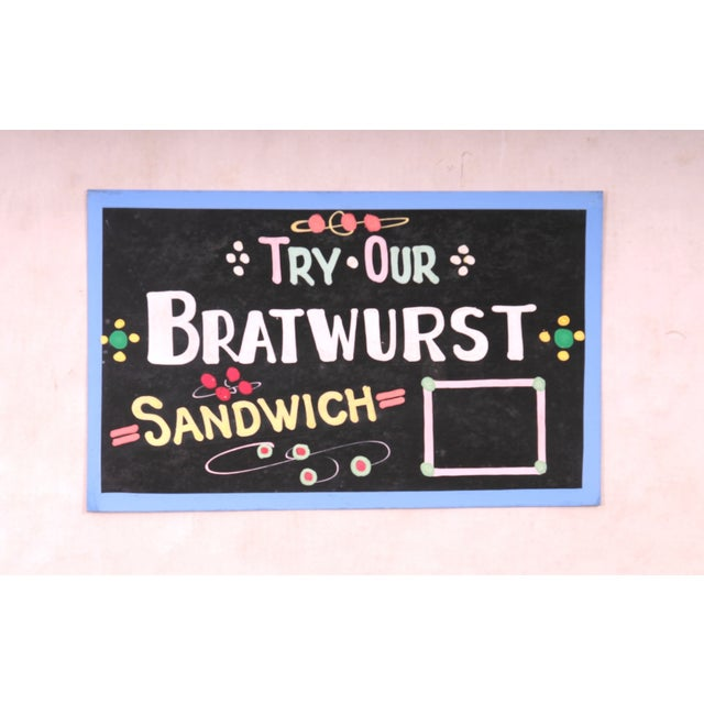 "Vintage, one-sided hand painted sign on chipboard saying ""Try Our Bratwurst Sandwich Sign"" ."