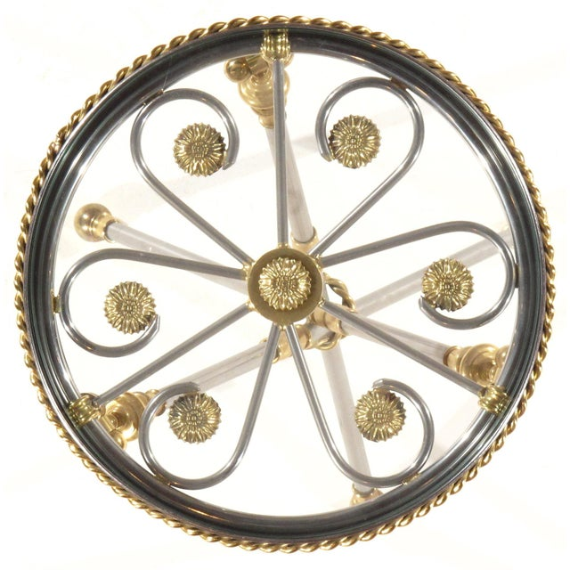 Whimsical tripod table of polished steel and brass. The pattern of a revolving wheel is insert in the steel gallery....