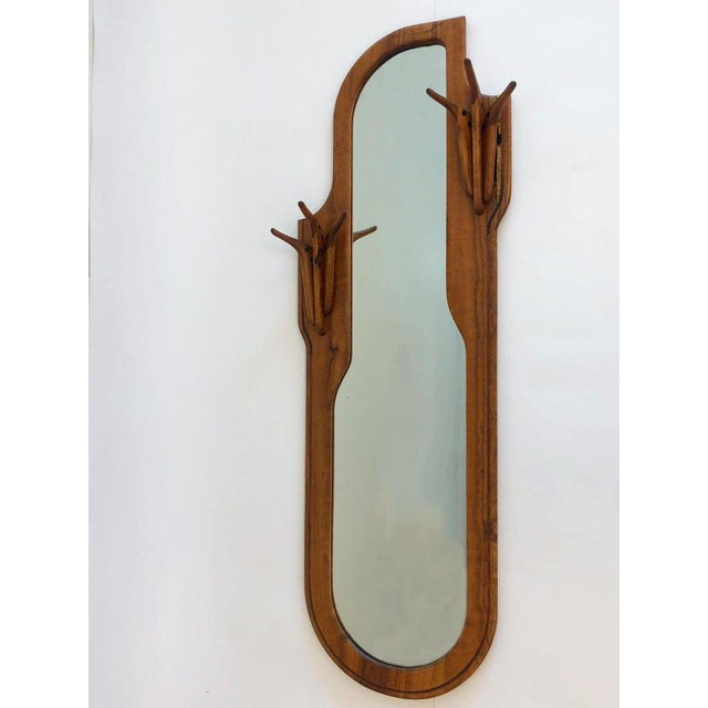 A spectacular American studio craftsman walnut mirror with a built in coat hanger. The mirror is Signed Charles B. Cobb...