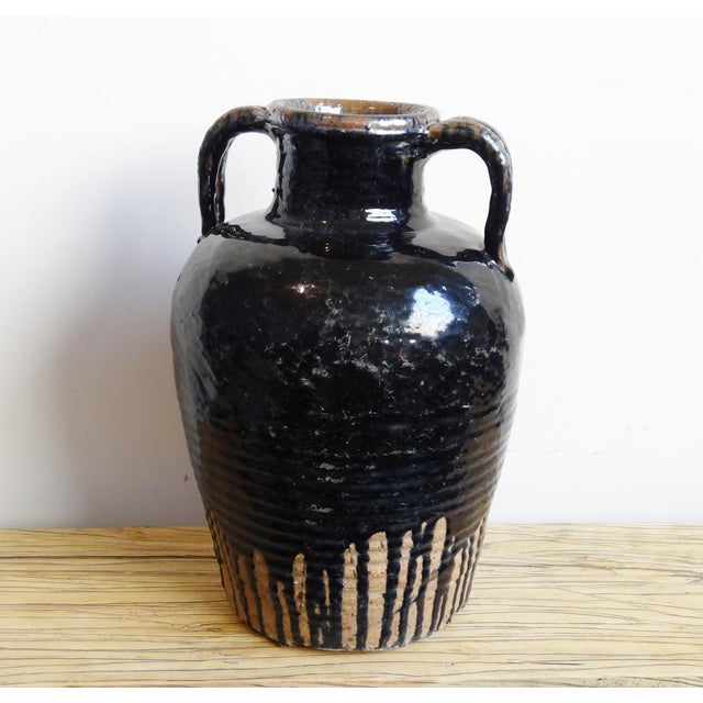 Ceramic wine jug with distressed black patina and finished in glazed porcelain finish. This classic and eclectic item can...