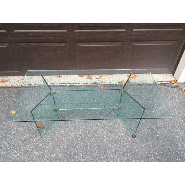 A beautiful 1970s Pace Collection side table with thick glass and shiny brass. The top has beveled edges, and the glass is...