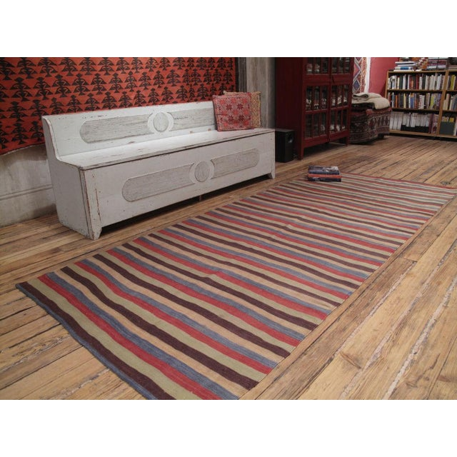 An old tribal floor cover with great wool and mellow colors.