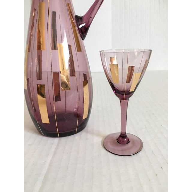 Wonderful vintage blown amethyst glass decanter with stopper and two matching cordial glasses decorated in gold. Note...