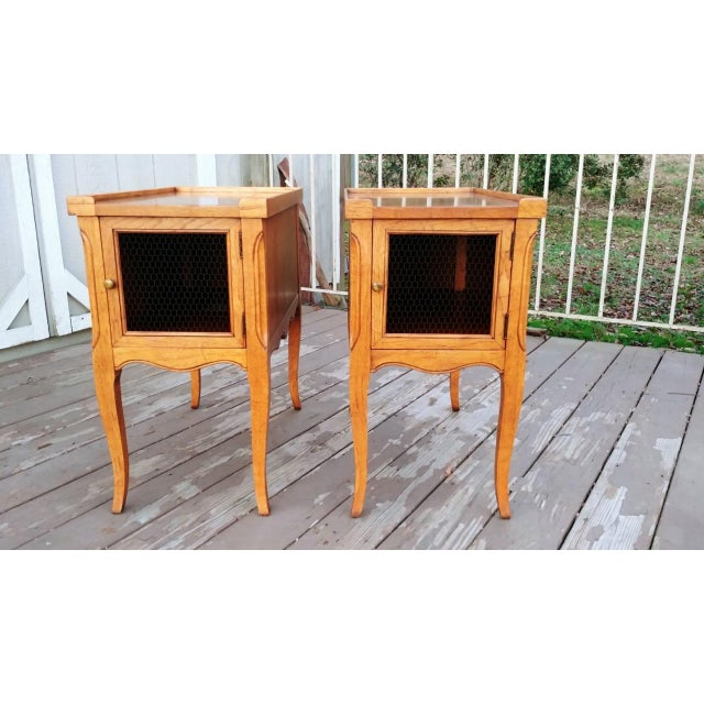 Item offered is a vintage pair of French style Walnut end tables with burl Walnut tops. Each has a wire inset front door...