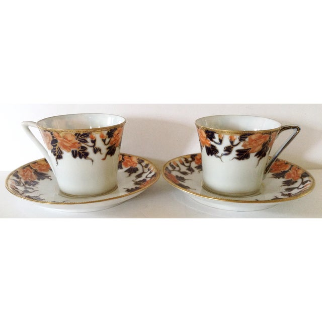 This pair of cups and saucers is egg shell thin as seen in the photo how transparent they are. Each decorated in a...
