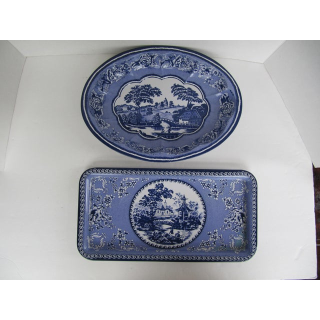 """Two blue and white """"transfer ware"""" serving pieces, a rectangle tray with flowers and a pagoda in the center and an oval..."""
