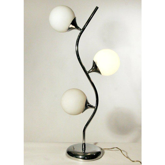 This 1970s vine-like table lamp in manner of Robert Sonneman features three illuminated glass globes affixed to chrome...