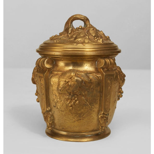 French Art Nouveau gilt bronze round box with 4 scrolls and a floral relief design with a cover (signed: MARIONNET)