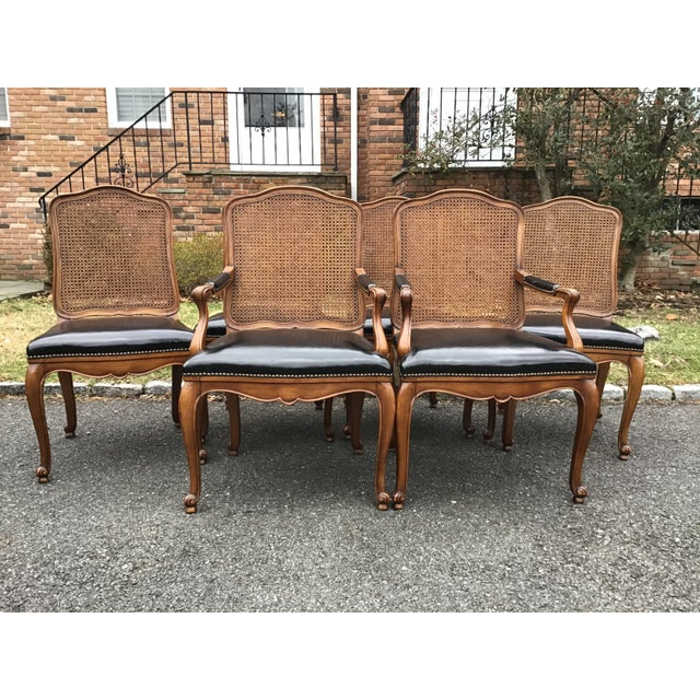 This is an amazing set of 6 Bodart French Louis XIV caned back, black leather upholstered dining chairs. I believe they...