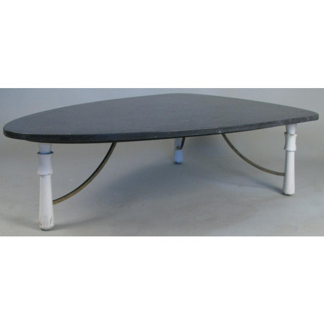 A beautiful 1950s triangular marble top cocktail table, with three leg base, the turned legs connected with brass...