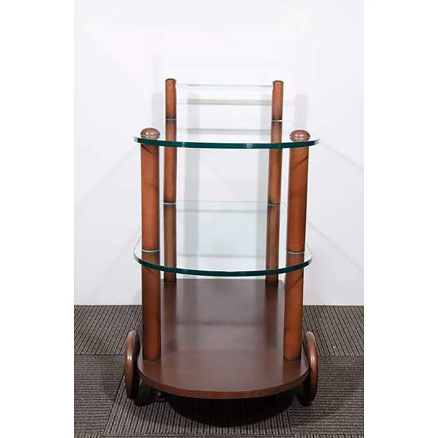 An Art Deco Gilbert Rohde bar cart, circa 1940s with all original glass including glass rod handle and wood finish.