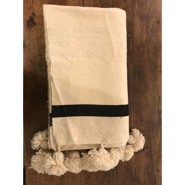Hand-woven cream Moroccan wool stripe throw blanket with poms. Hand spun and crafted with age old techniques by multi...