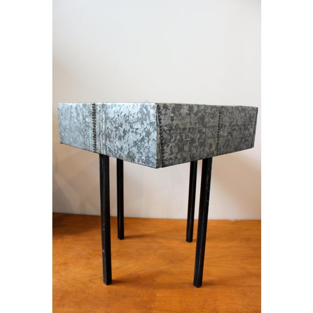 This is a contemporary artisan made end table. The piece features a metal top and hammered nail detail. Made in USA