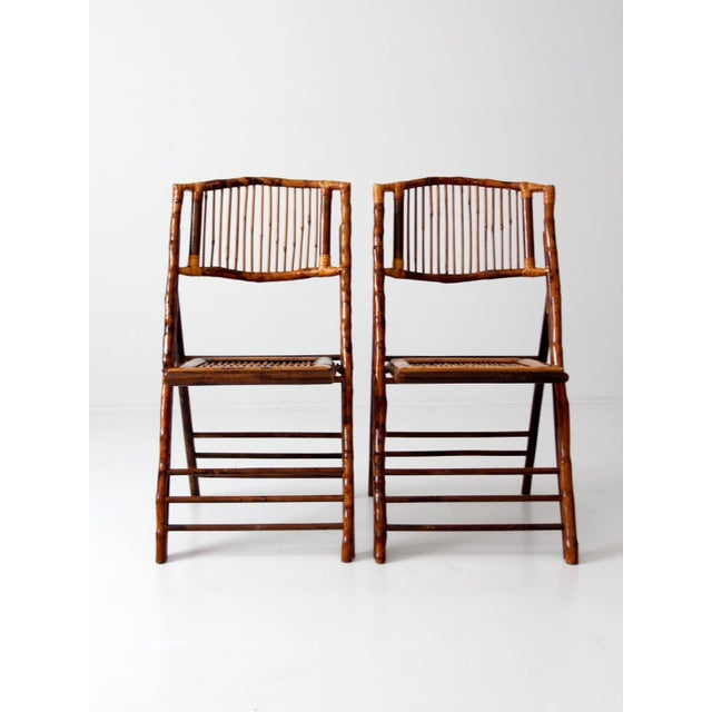 This is a pair of vintage bamboo folding chairs. The lacquered chairs feature backs and seats with slender reed slatting....