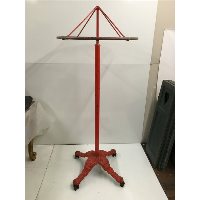 "Offered is a revolving clothing rack with wheeled cast iron base. Can be adjusted to accommodate a 59"" or 69"" drop."