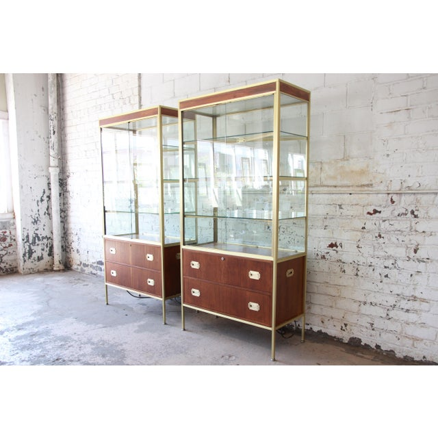 Offering an extremely rare and exceptional pair of mid-century Hollywood Regency Campaign style lighted display cabinets...