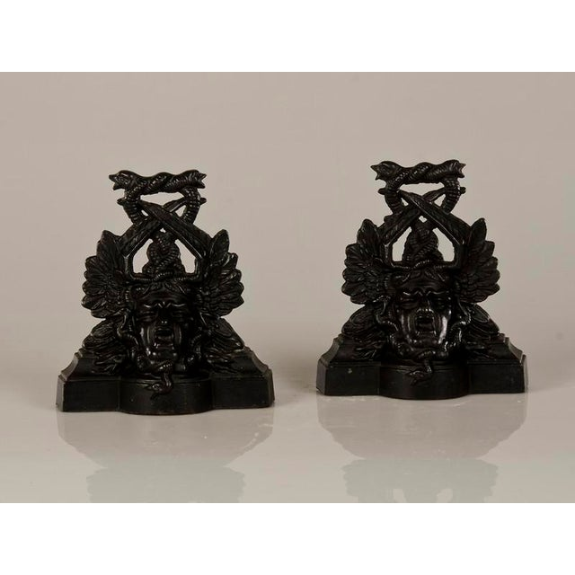 A pair of extraordinary cast iron door stops with an entire portrait bust of Medusa encircled by serpents in a sinuous...