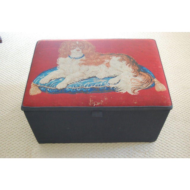Hinged storage box/ottoman/coffee table upholstered in black linen with a 19th century needlepoint top depicting a King...