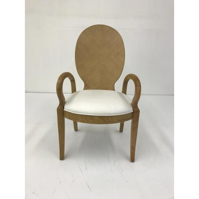 The Oak Dining Arm Chair is a first quality market sample that features a White fabric with a Blonde Cerused Finish.