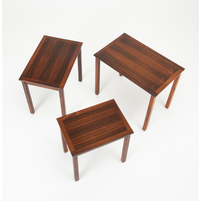 A set of Danish nesting tables in rosewood. Table design has square, slightly recessed legs, and a tabletop beautifully...