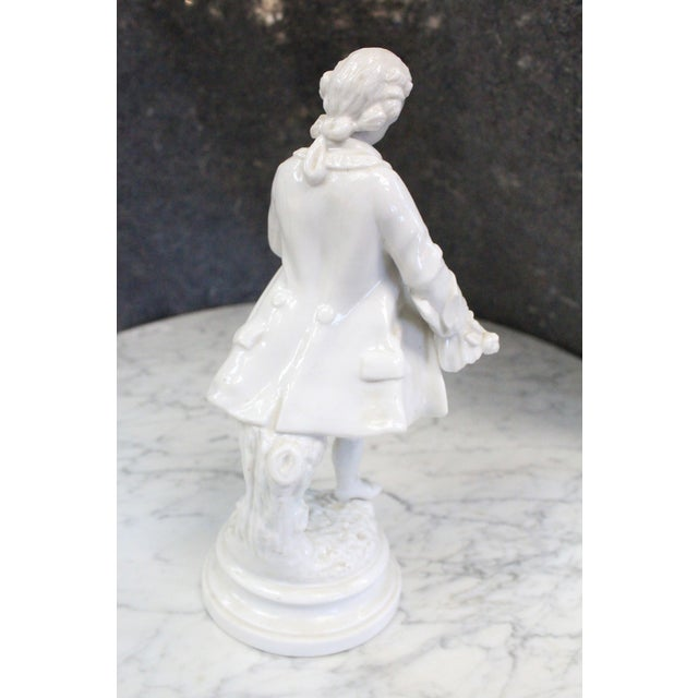 White porcelain figurine of Hamilton walking in traditional Colonial dress on solid base.