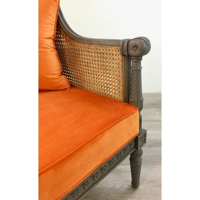 A chic juxtaposition of classic French and modern, gray finished carved wood frame, cane back, and orange velvet cushion...