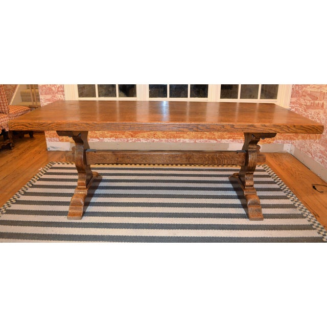 This is a beautiful French solid wood trestle farm table with wood stretcher. This is with pegged mortise and tenon...