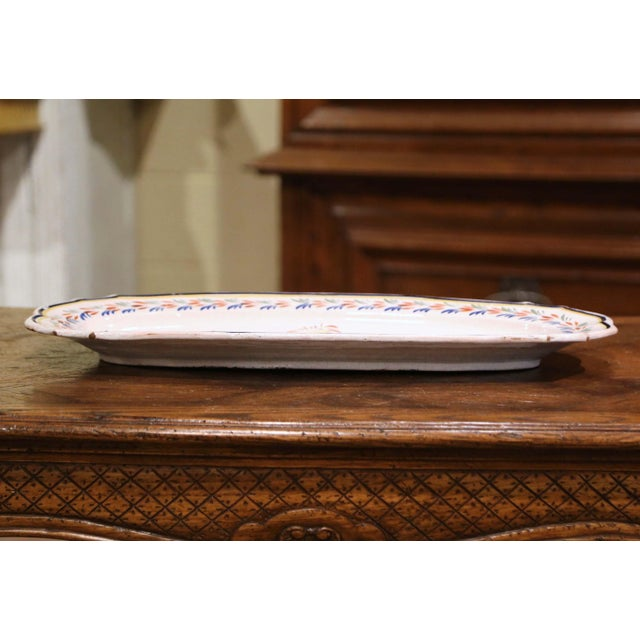 This colorful ceramic platter was created in Brittany, France, circa 1950. Oval in shape, the large faience tray is...