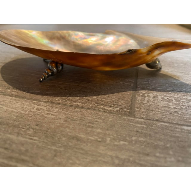Very nicely made shell soap dish. The shell has some rainbow flash in it. And the swirly metal chrome legs are a nice...