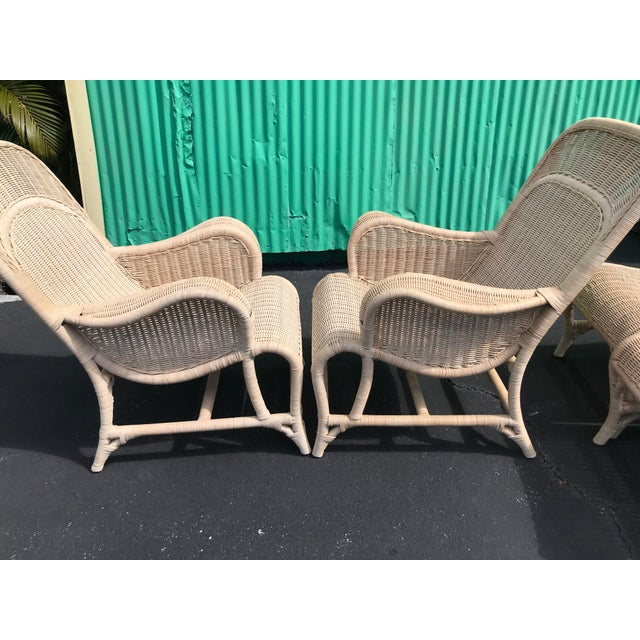 Beautiful set of wicker sling back chairs and ottomans from the 80's by Robb & Stucky. These do have a pink chair cushion...