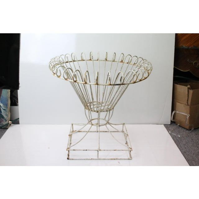 Oversized and elaborate rustic iron plant stand in white. Geometric base with frond like curls on top.