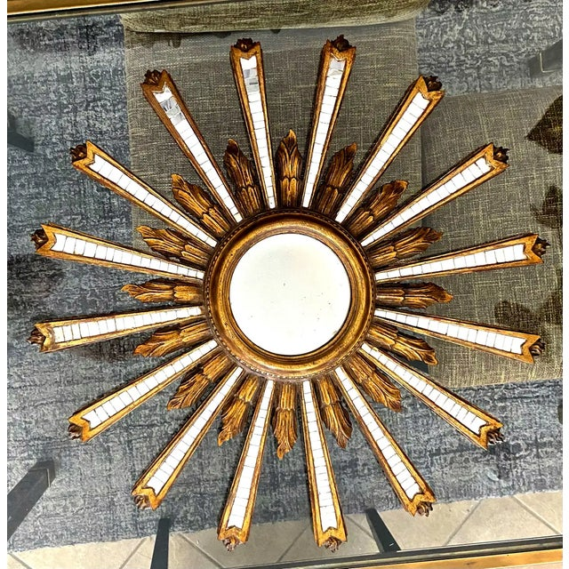 Large Italian hand carved gilt wood and gesso sunburst or starburst wall mirror with convex bulls eye center mirror. The...