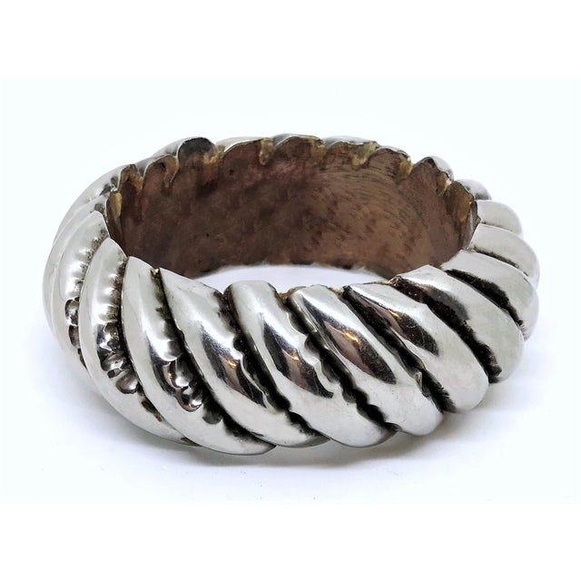 "Chunky silver-plated copper over a carved wood bangle in a raised design. The interior circumference is 7.75"" and measures..."
