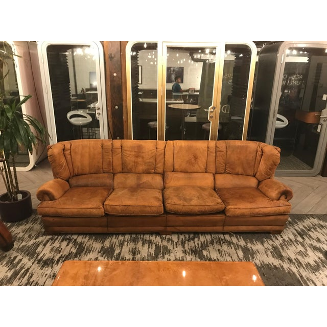 Large leather sofa from France, circa 1950. This piece holds character and a beautiful rustic appeal. Complimentary to any...