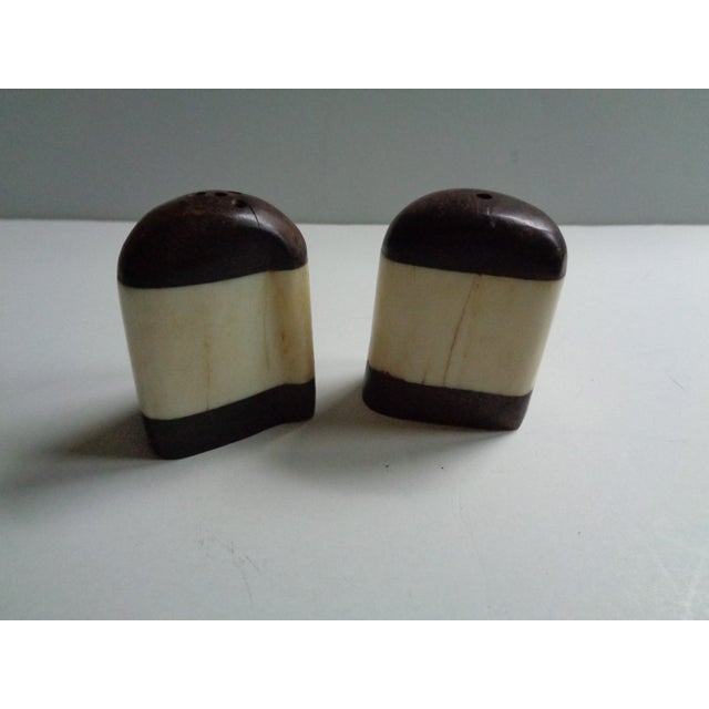 A rustic set of vintage mid-century salt and pepper shakers, made of African wood and reclaimed horn. Etched with a rhino...