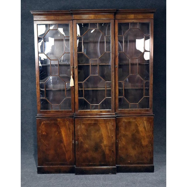 Baker Georgian style flame mahogany breakfront with 3 doors containing 9 shelves on top and 3 doors each containing 1...